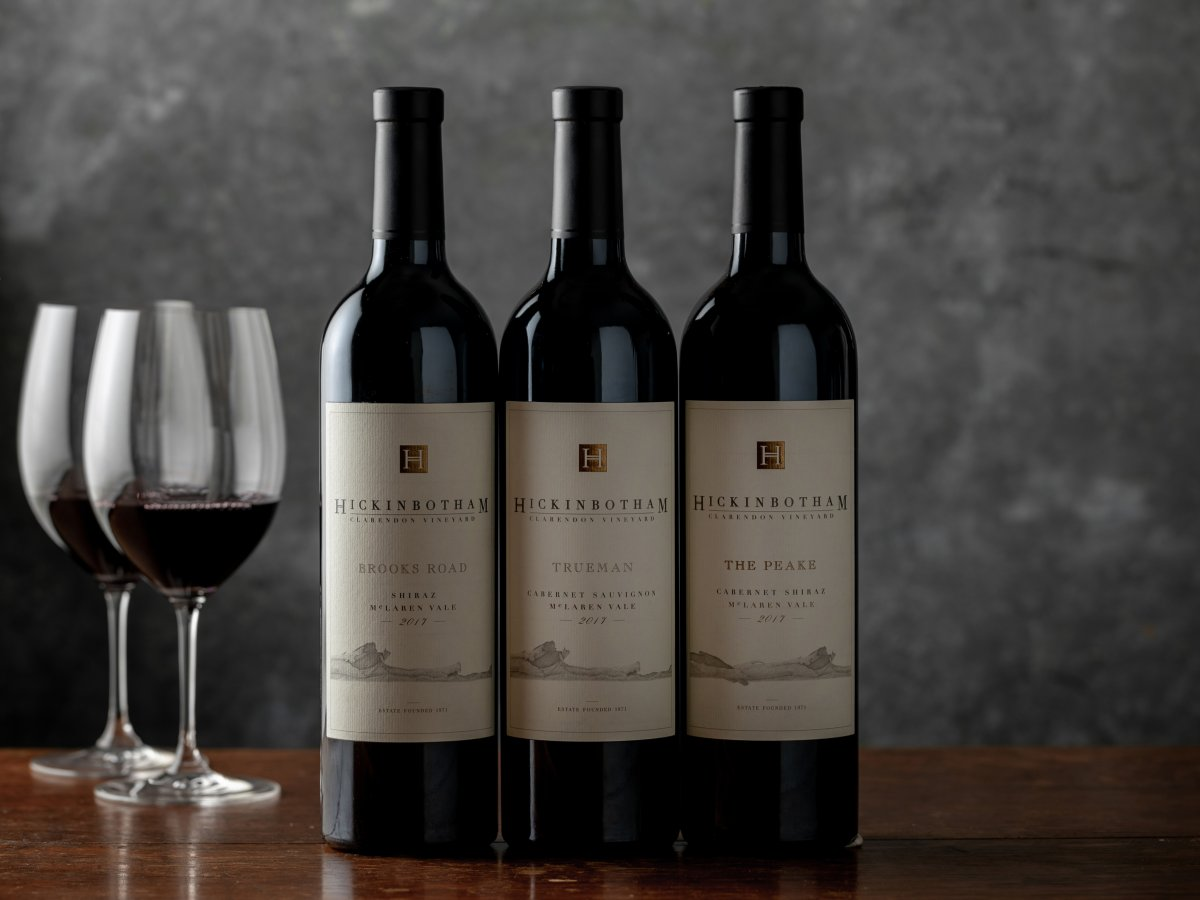 Three bottles of Hickinbotham wine on a table next to two wine glasses